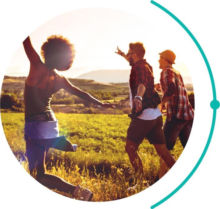 three friends running through a field